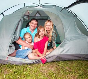 Family with children in a tent. Camping. Happy parents with kids at summer vacations